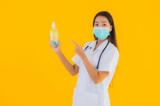 Porträt schöne junge asiatische ärztin tragen maske mit alkoholgel