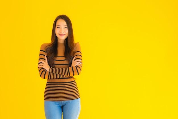 Porträt schöne junge asiatische erwachsene frau lächeln mit vielen aktion auf gelber wand