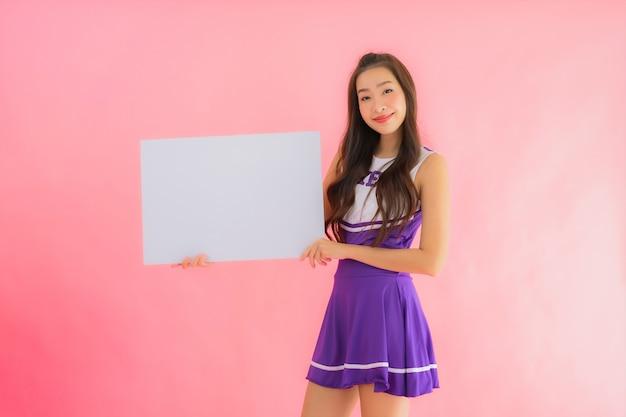 Porträt schöne junge asiatische frau cheerleader lächeln zeigen leere weiße tafel