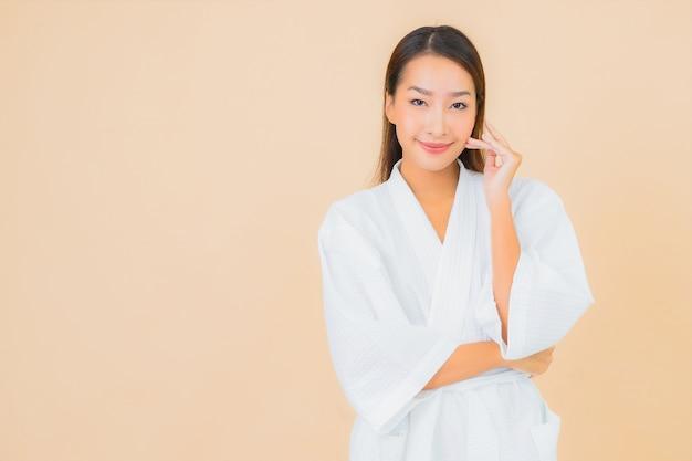 Porträt schöne junge asiatische frau, die bademantel mit lächeln auf beige trägt