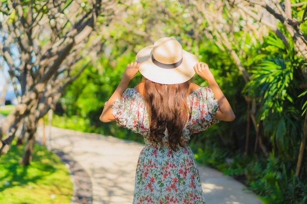 Porträt schöne junge asiatische frau, die mit glücklich um gartenblick im freien geht