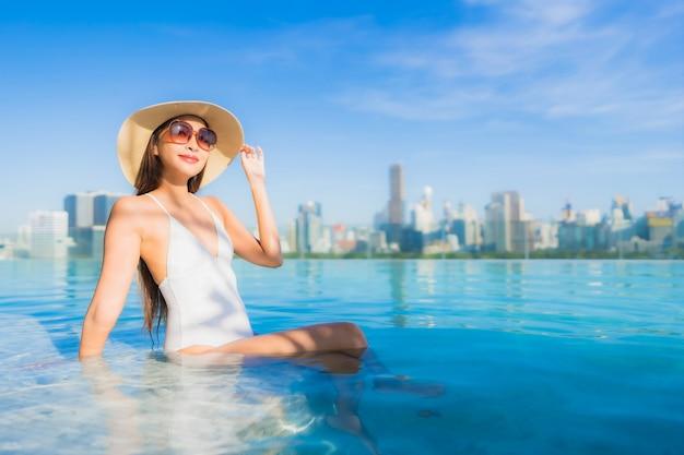 Porträt schöne junge asiatische frau, die sich um freibad mit blick auf die stadt entspannt