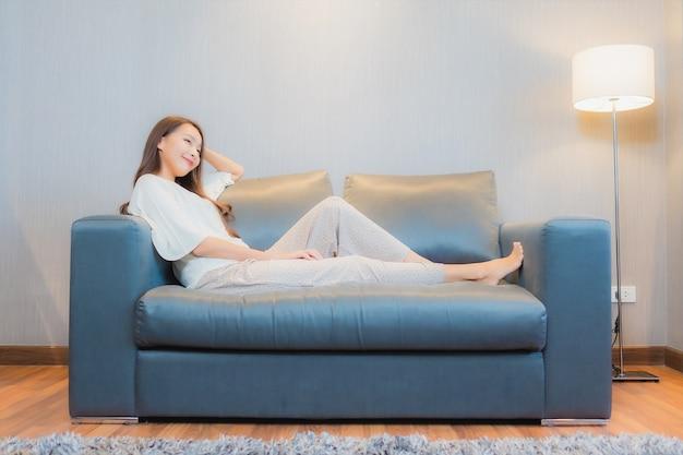 Porträt schöne junge asiatische frau entspannen auf sofa im wohnzimmer interieur