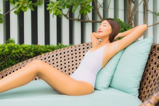 Porträt schöne junge asiatische frau entspannen freizeit um freibad im hotel resort für reiseurlaub