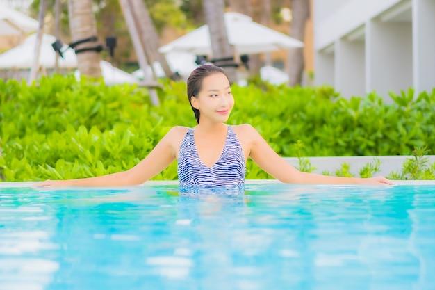 Porträt schöne junge asiatische frau entspannen freizeit um freibad mit meer ozean strand