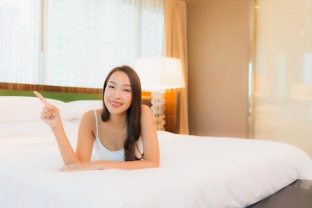 Porträt schöne junge asiatische frau entspannen lächeln auf dem bett im schlafzimmer interieur