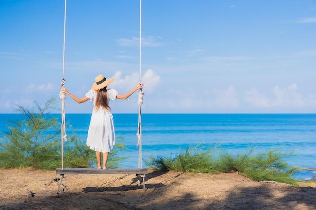 Porträt schöne junge asiatische frau entspannen lächeln auf schaukel um strand meer ozean für naturreisen im urlaub