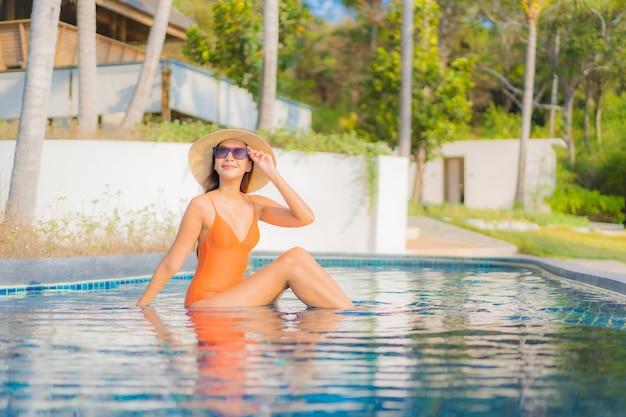 Porträt schöne junge asiatische frau entspannen lächeln freizeit um freibad im hotel resort im reiseurlaub Kostenlose Fotos