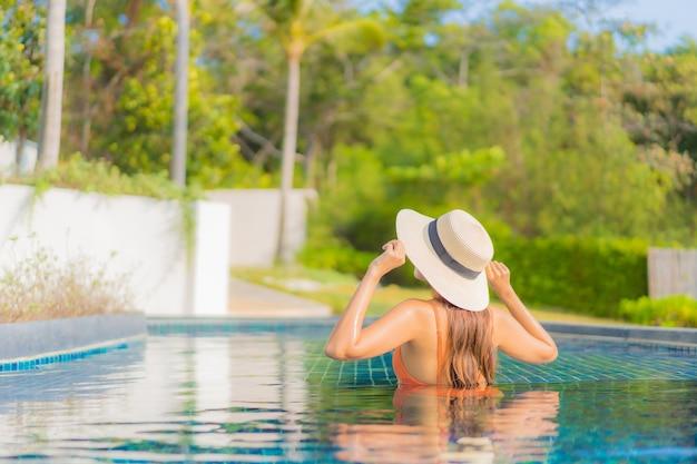 Porträt schöne junge asiatische frau entspannen lächeln freizeit um freibad im hotel resort im reiseurlaub