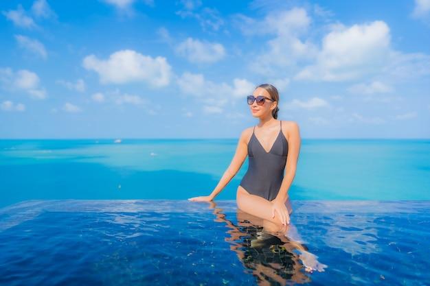 Porträt schöne junge asiatische frau entspannen lächeln freizeit um freibad im resort hotel mit meerblick