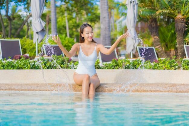 Porträt schöne junge asiatische frau entspannen lächeln freizeit um freibad mit meer ozean im reiseurlaub Kostenlose Fotos