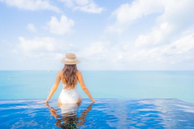 Porträt schöne junge asiatische frau entspannen lächeln freizeit um freibad mit meer ozean im reiseurlaub