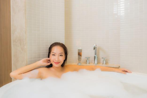 Porträt schöne junge asiatische frau entspannen lächeln in der badewanne am badezimmer interieur