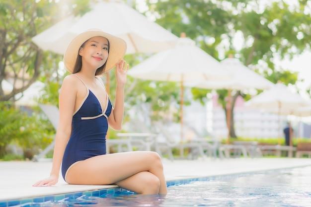 Porträt schöne junge asiatische frau entspannen lächeln um freibad im hotel resort auf urlaubsreise
