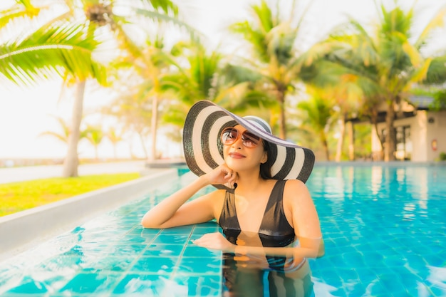 Porträt schöne junge asiatische frau entspannen um außenpool im hotelresort mit palme bei sonnenuntergang oder sonnenaufgang