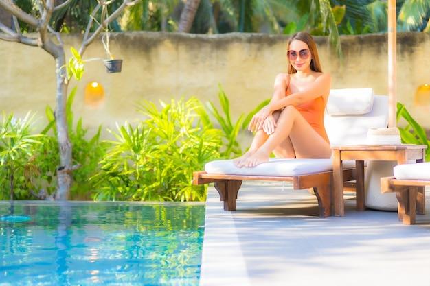 Porträt schöne junge asiatische frau genießen entspannen um schwimmbad für freizeiturlaub