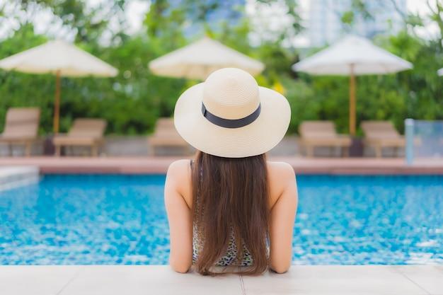 Porträt schöne junge asiatische frau im freien im schwimmbad in urlaubsreise entspannen