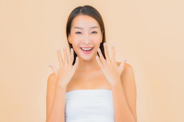 Porträt schöne junge asiatische frau im spa mit natürlichem make-up auf beige
