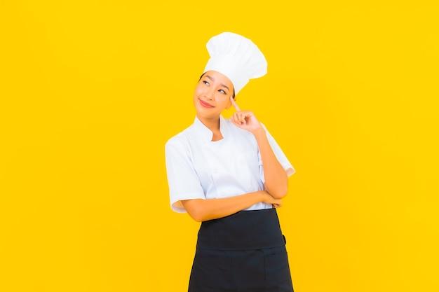 Porträt schöne junge asiatische frau in koch- oder kochuniform mit hut auf gelbem isoliertem hintergrund