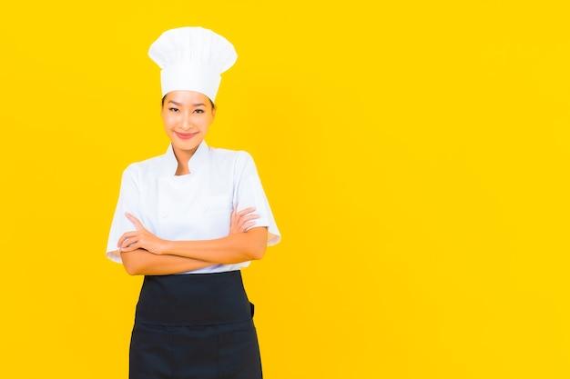 Porträt schöne junge asiatische frau in koch- oder kochuniform mit hut auf gelbem isoliertem hintergrund Kostenlose Fotos