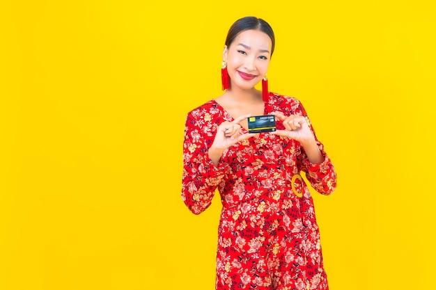 Porträt schöne junge asiatische frau kreditkarte für das einkaufen auf gelber isolierter wand
