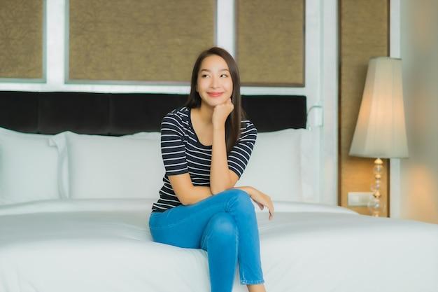 Porträt schöne junge asiatische frau lächeln entspannen auf dem bett im schlafzimmer interieur