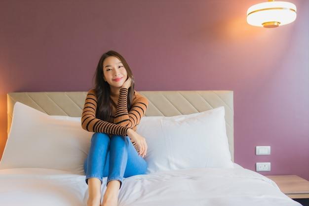 Porträt schöne junge asiatische frau lächeln entspannen auf dem bett