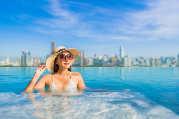 Porträt schöne junge asiatische frau lächeln entspannen freizeit um freibad mit blick auf die stadt