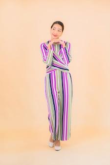 Porträt schöne junge asiatische frau lächeln entspannen in aktion auf farbe