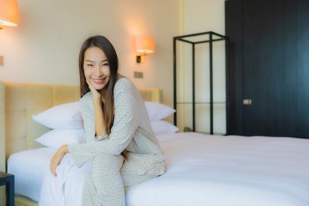 Porträt schöne junge asiatische frau lächeln glücklich entspannen auf dem bett