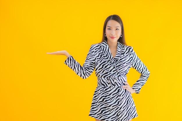 Porträt schöne junge asiatische frau lächeln glücklich mit aktion auf gelb