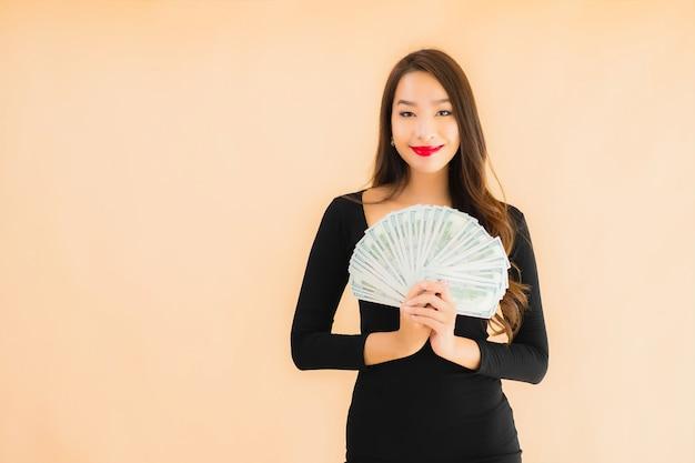 Porträt schöne junge asiatische frau lächeln glücklich mit geld und bargeld