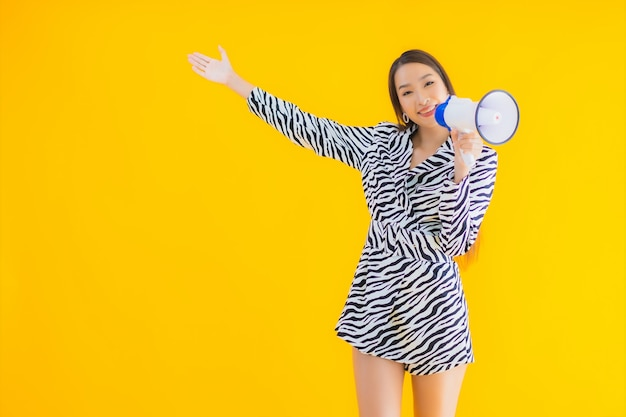 Porträt schöne junge asiatische frau lächeln glücklich mit megaphon auf gelb