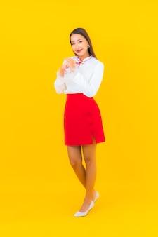 Porträt schöne junge asiatische frau lächeln in aktion auf gelb