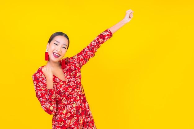 Porträt schöne junge asiatische frau lächeln in aktion im chinesischen neujahrskonzept auf farbwand