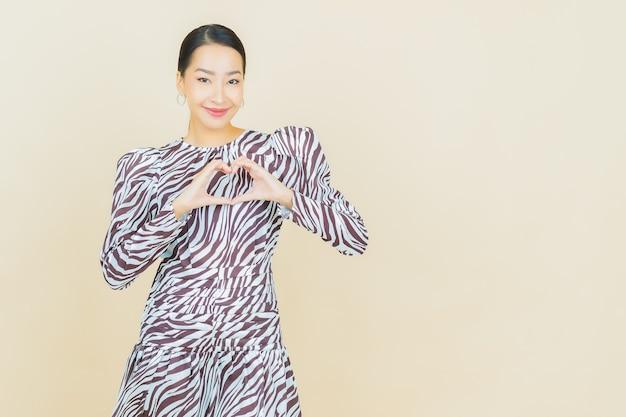 Porträt schöne junge asiatische frau lächeln mit aktion auf beige