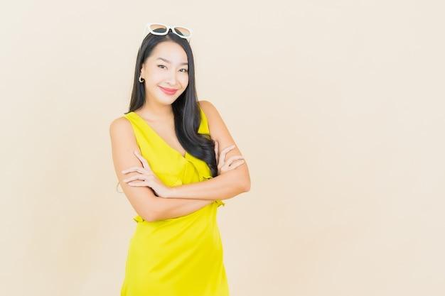 Porträt schöne junge asiatische frau lächeln mit aktion auf creme wand