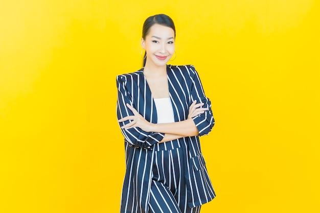Porträt schöne junge asiatische frau lächeln mit aktion auf farbhintergrund