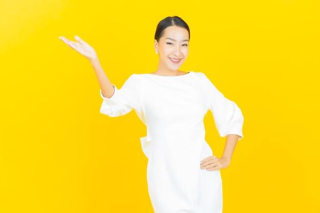 Porträt schöne junge asiatische frau lächeln mit aktion auf gelb with
