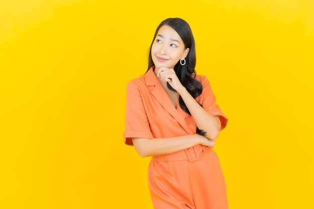 Porträt schöne junge asiatische frau lächeln mit aktion auf gelb