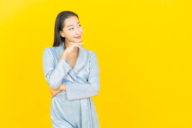 Porträt schöne junge asiatische frau lächeln mit aktion auf gelber wand