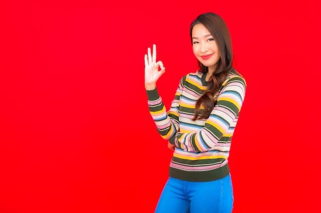 Porträt schöne junge asiatische frau lächeln mit aktion auf rote isolierte wand