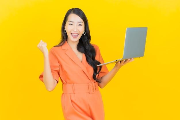 Porträt schöne junge asiatische frau lächeln mit computer laptop auf gelb