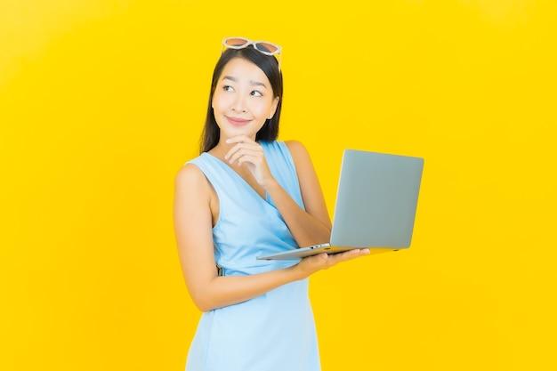 Porträt schöne junge asiatische frau lächeln mit computer laptop auf gelbe isolierte wand