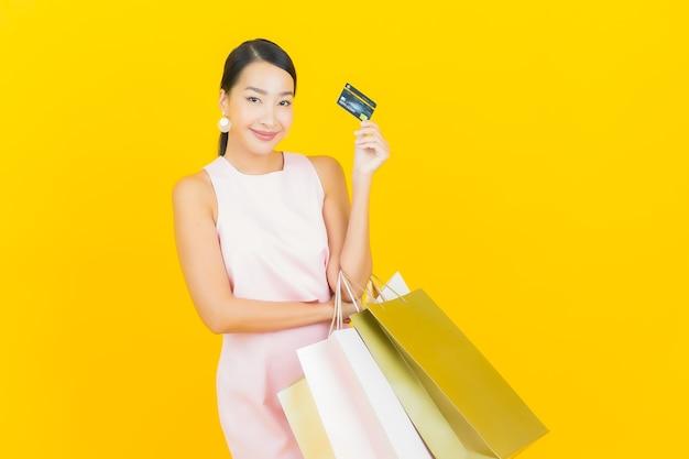 Porträt schöne junge asiatische frau lächeln mit einkaufstasche auf gelb