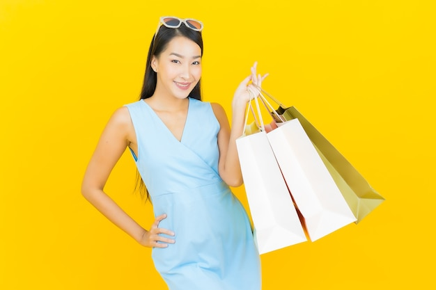 Porträt schöne junge asiatische frau lächeln mit einkaufstasche auf gelber farbe wand