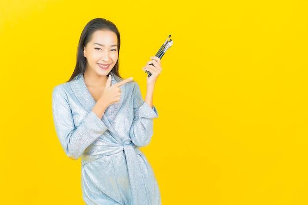 Porträt schöne junge asiatische frau lächeln mit kosmetischen make-up pinsel auf gelbe wand