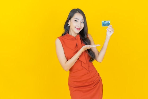 Porträt schöne junge asiatische frau lächeln mit kreditkarte auf gelb