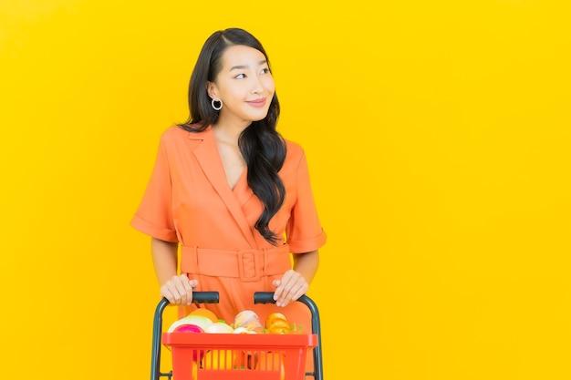Porträt schöne junge asiatische frau lächeln mit lebensmittelkorb vom supermarkt auf gelb