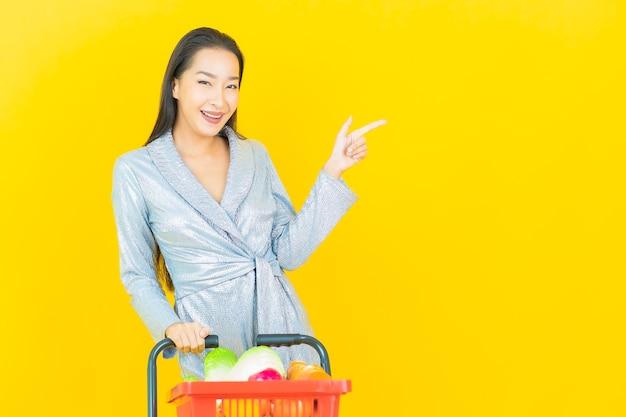 Porträt schöne junge asiatische frau lächeln mit lebensmittelkorb vom supermarkt auf gelber wand